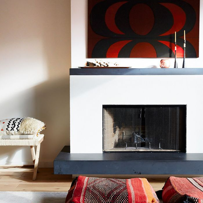 Cozy Home: Two patterned, square floor pillows in front of a fireplace