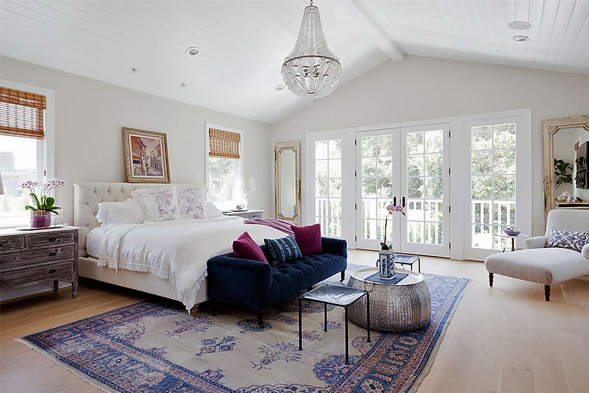 An airy all-white bedroom with a chandelier and navy tufted velvet sofa.