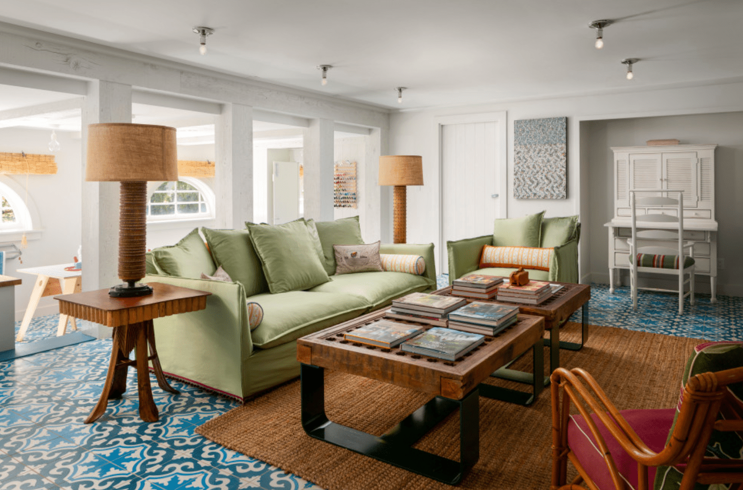 A spacious basement living room lit with semi-flush mounts and large table lamps