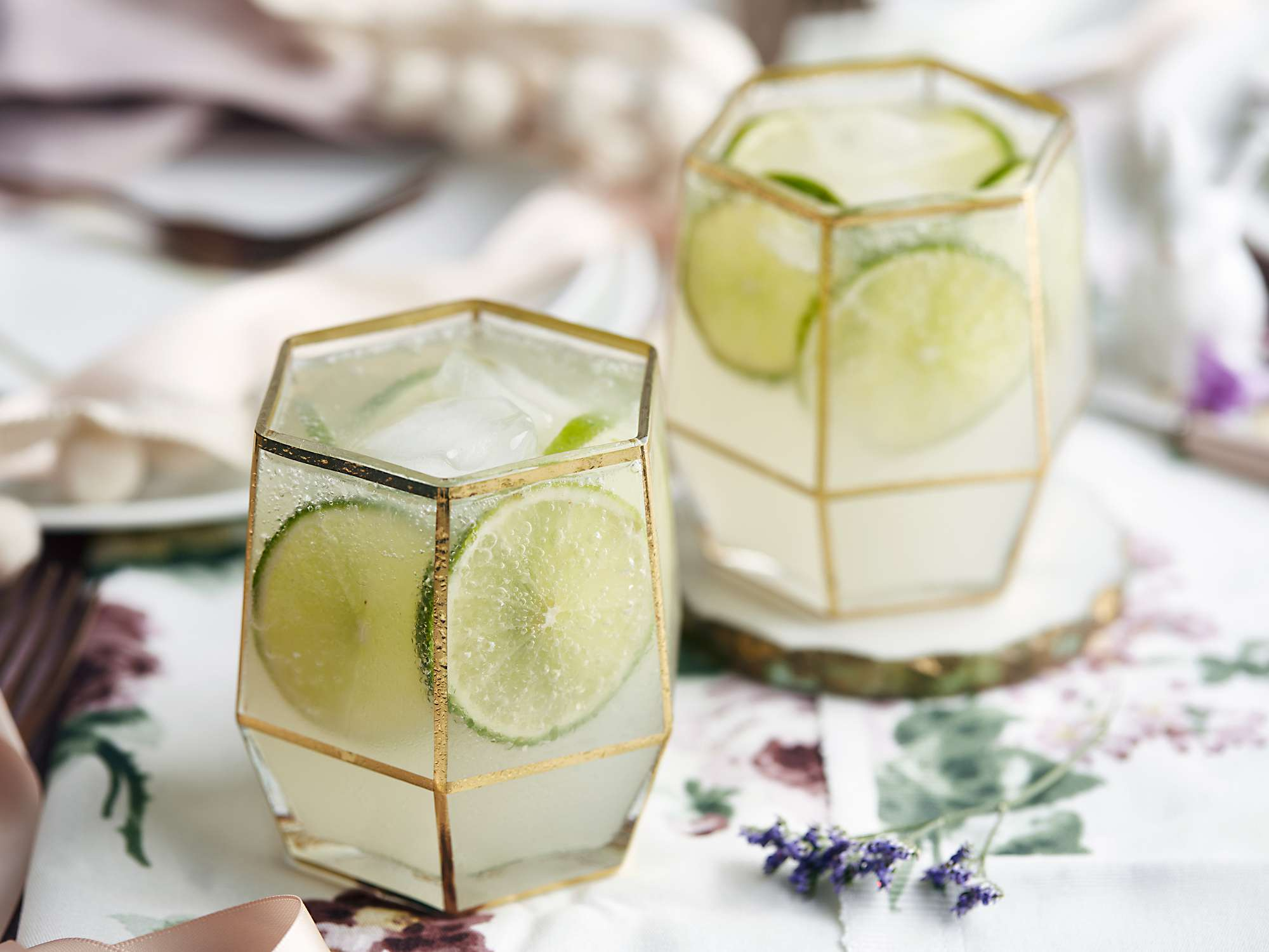 Two beverages with slices of lime on floral table cloth