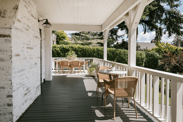 A wraparound porch with several dining and seating areas