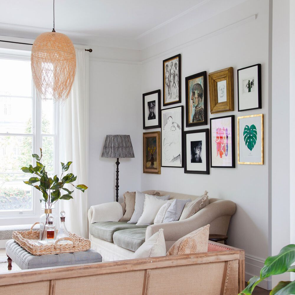 Eclectic living room with framed art gallery wall, mix-and-match furniture