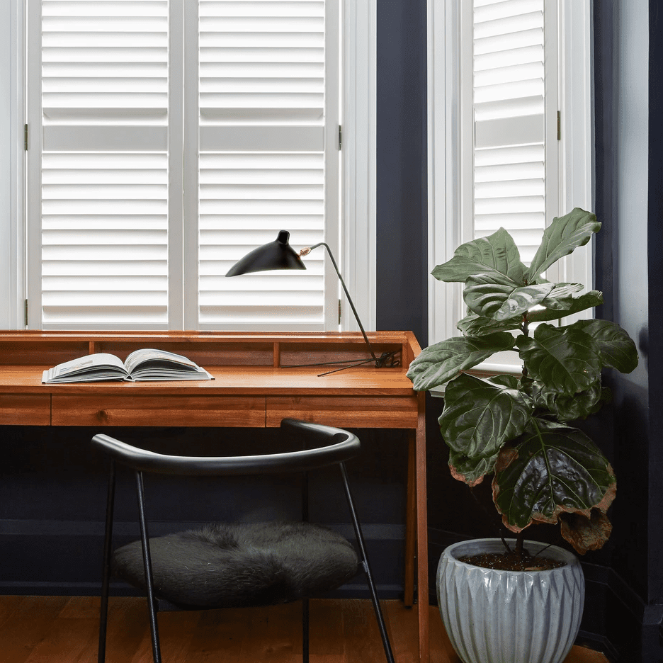 A small navy nook that's been transformed into a home office with a desk, a task lamp, a chair, and a plant
