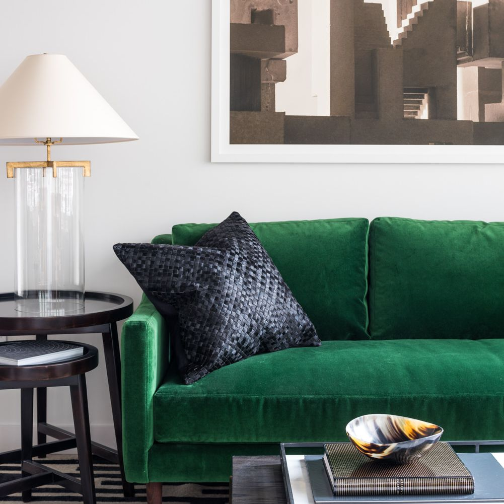 Living room with green couch, black-and-white area rug