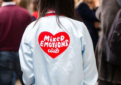 Woman wearing a jacket that reads mixed emotions club