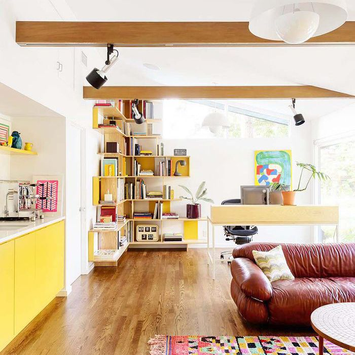 an open loft space with leather sofa and yellow kitchen cabinets