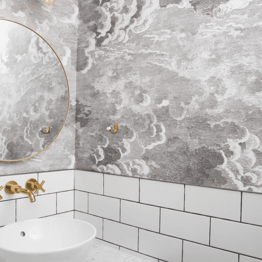 A powder room with grayscale wind gust wallpaper lining the walls