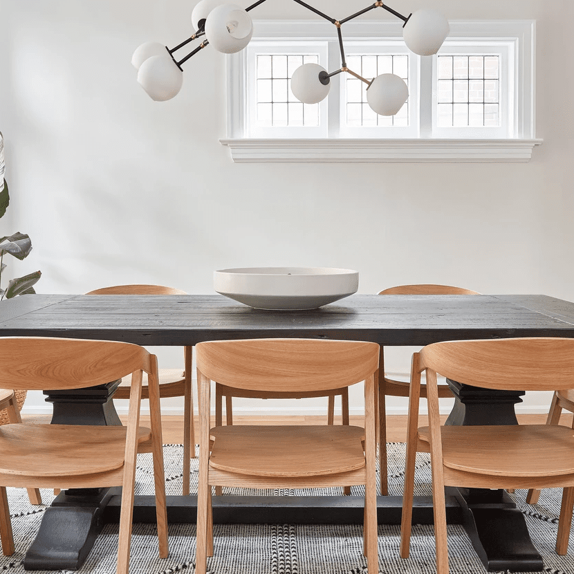 A black dining room table topped with a striking white ceramic bowl