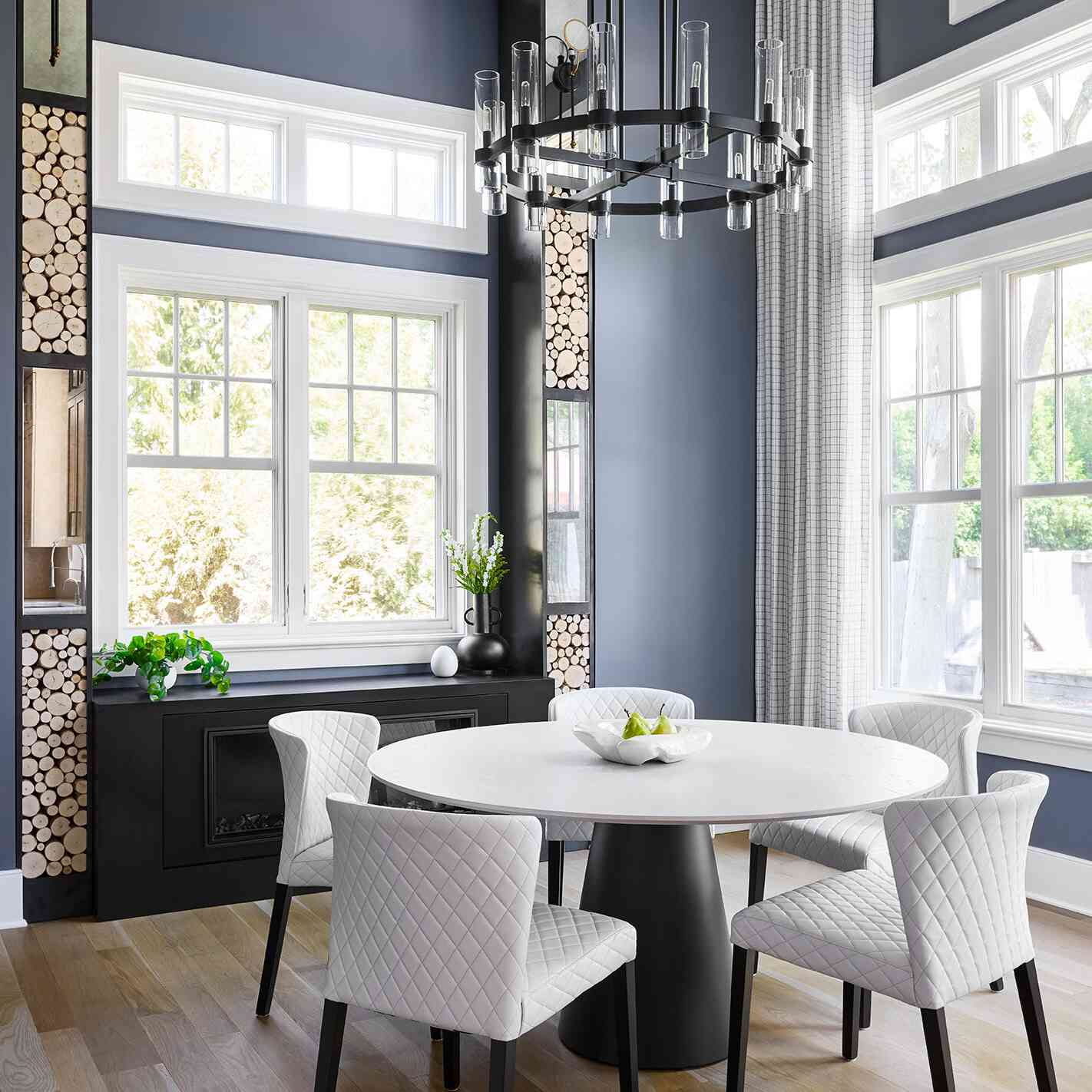 A dining room with blue-gray walls broken up by white trim