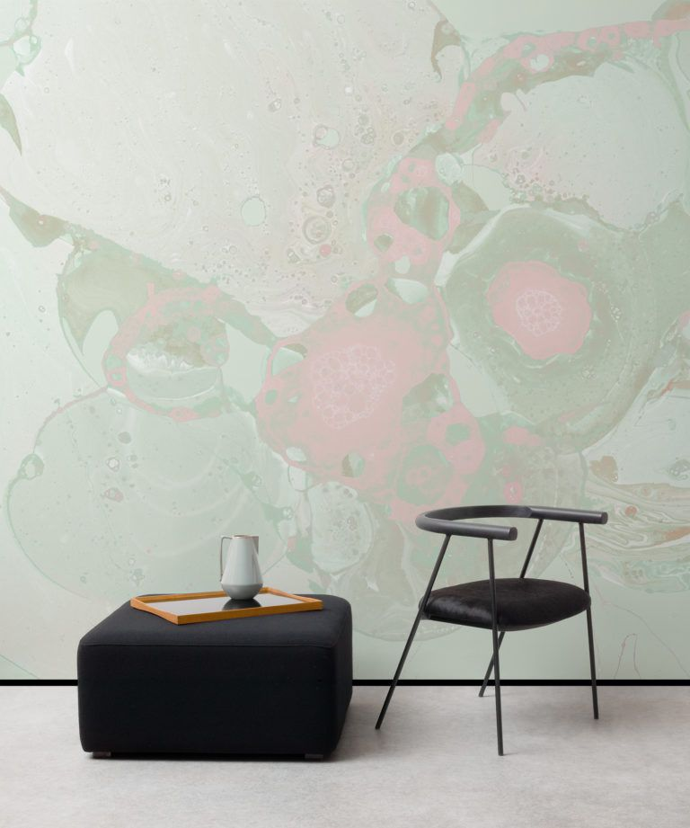 A pink and green marbled wallpaper mural behind a black square ottoman and black accent chair.