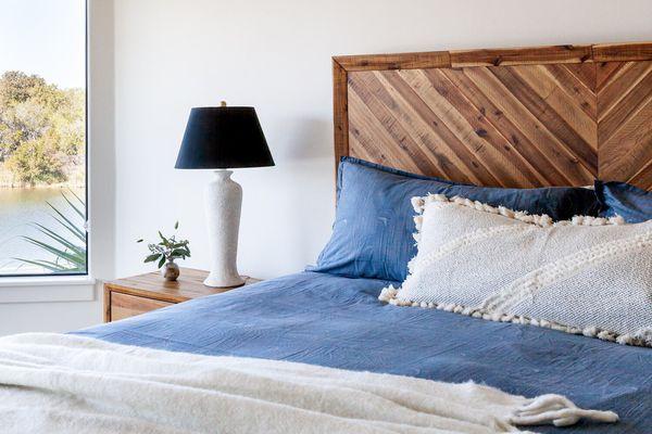 Blue linen bed on wooden bed frame.