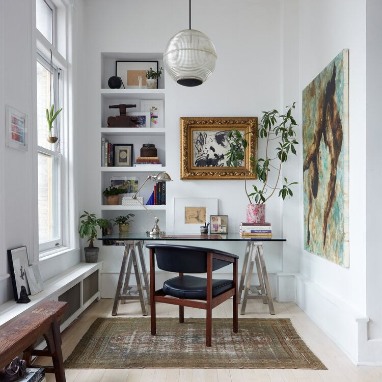 A narrow home office with a desk, art, and a bold pendant light