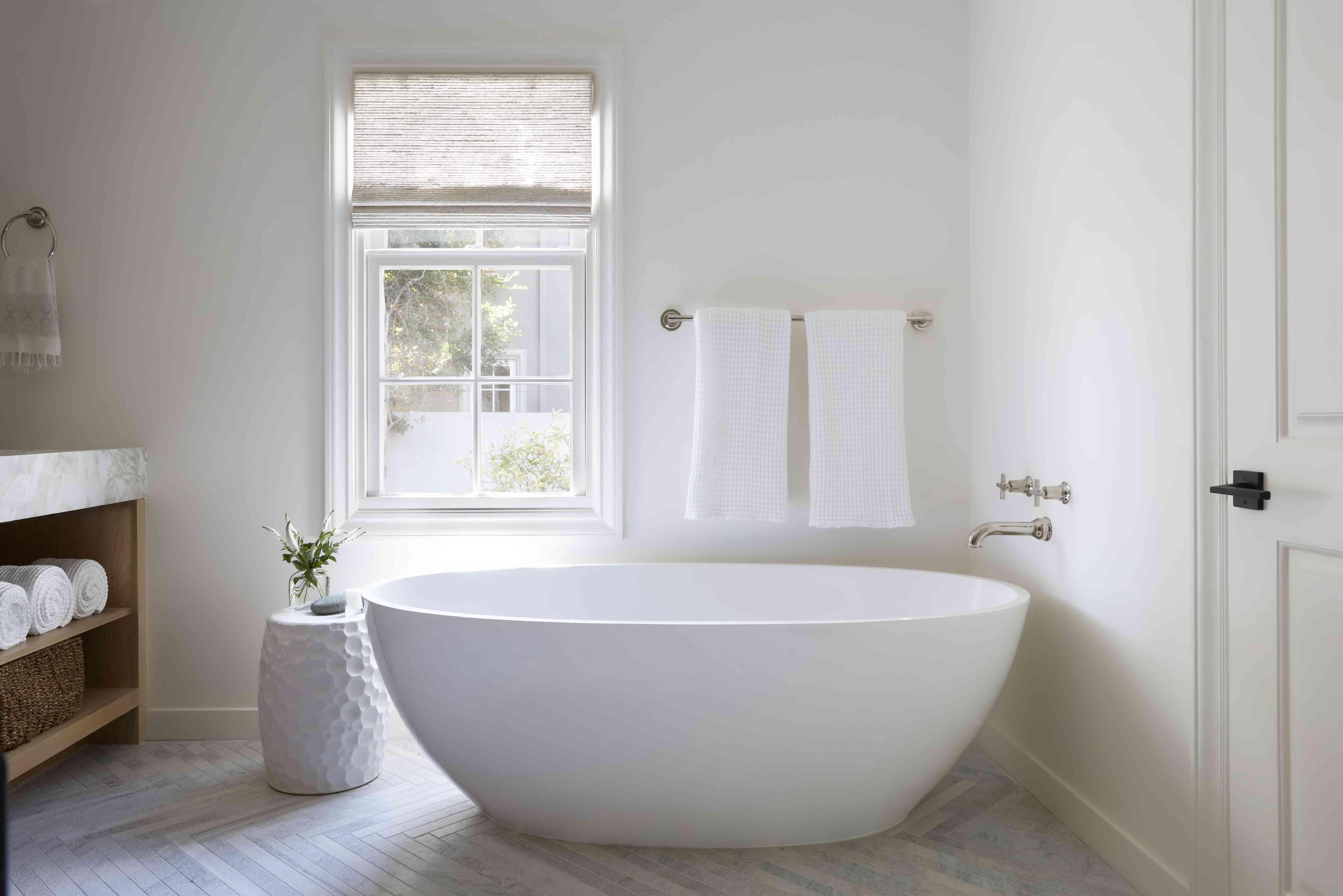 Porcelain freestanding bathtub under a widow.