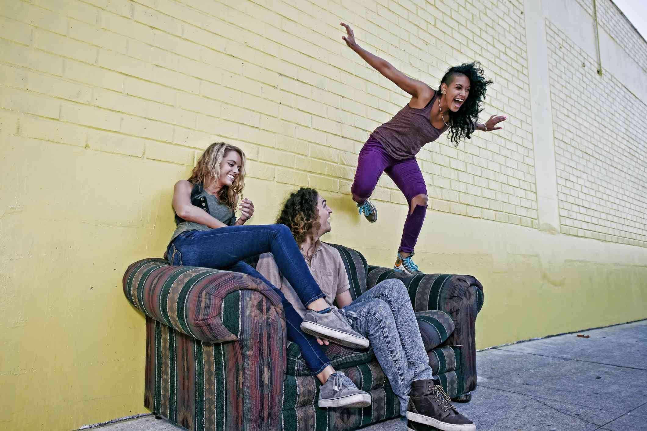 Woman jumps from sofa, friends watch on