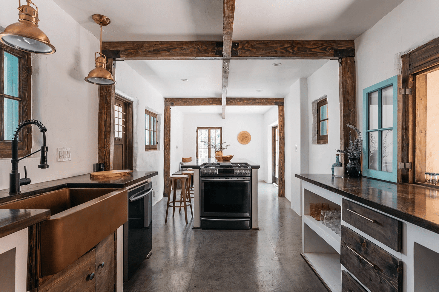 An open-concept kitchen with ceilings lined with exposed wood beams