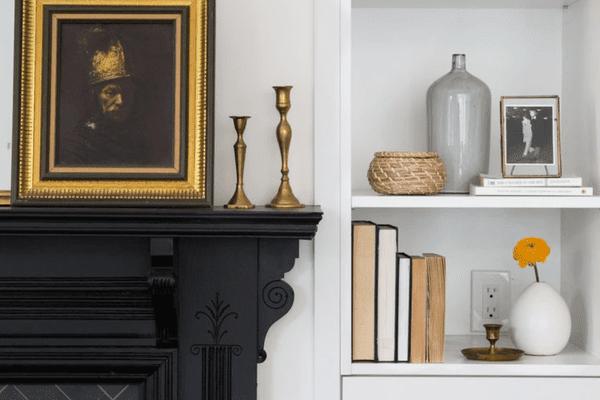 Decor on shelf and black fireplace mantle.v