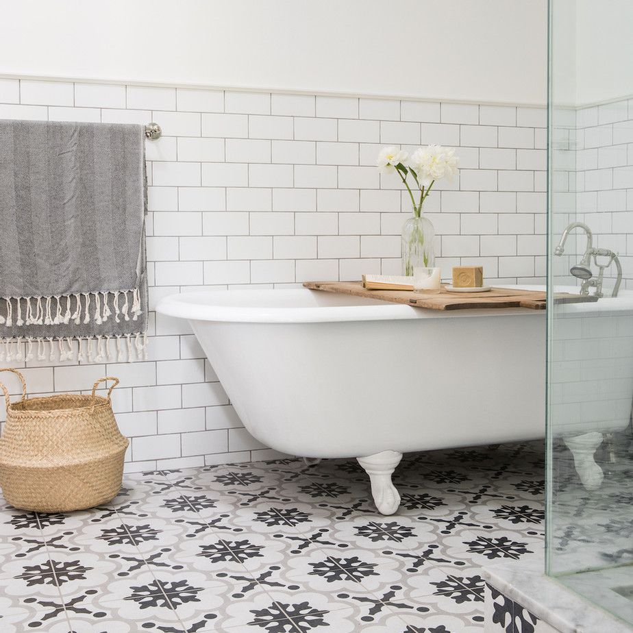 White bathroom with clawfoot tub and bath board with flowers, soap, a candle, and book.
