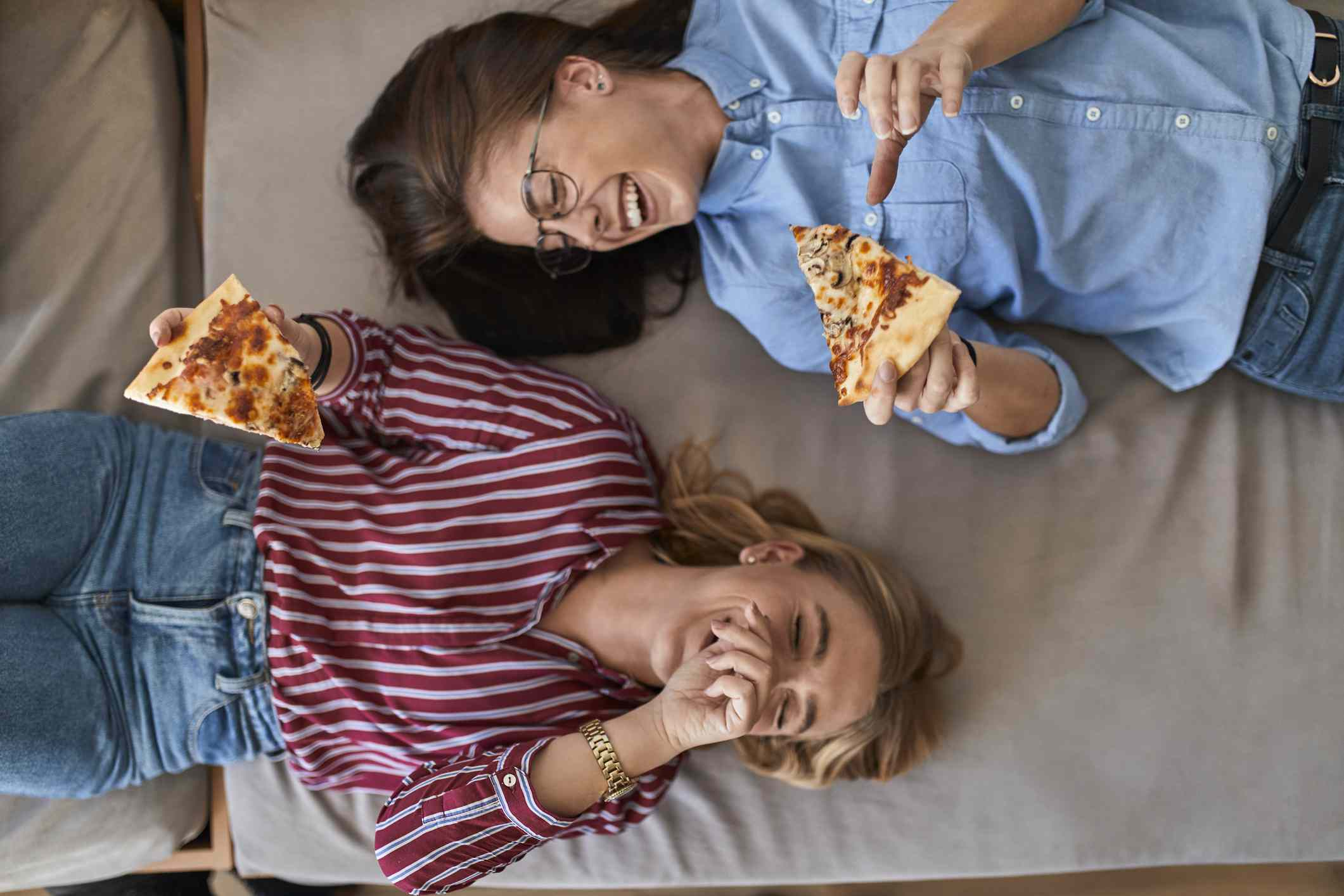 two women in bed with pizza