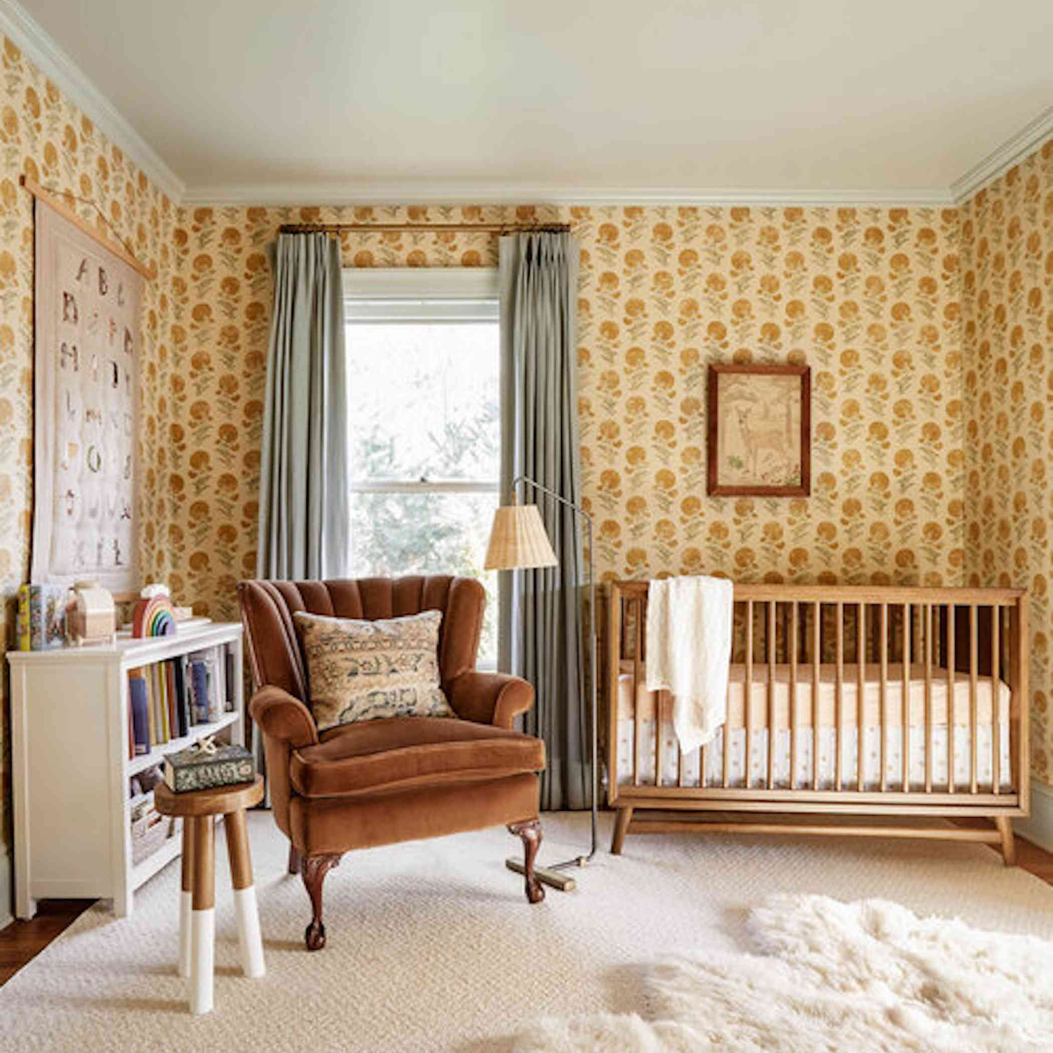 Vintage inspired nursery with yellow floral wallpaper.