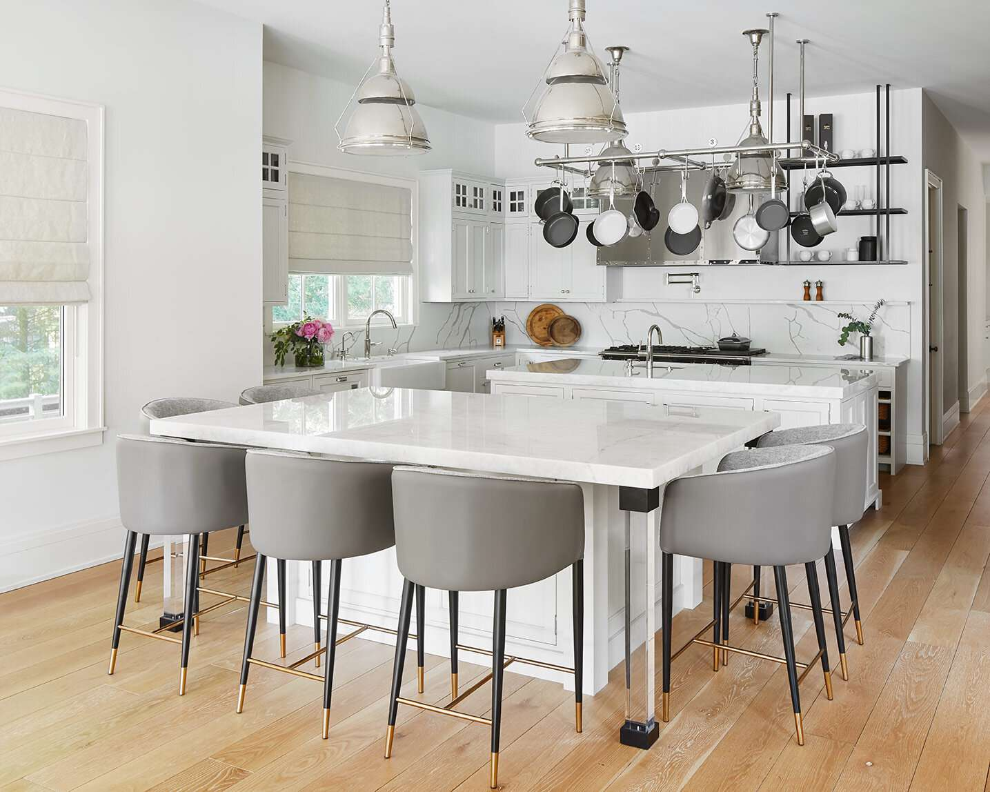 White kitchen with stainless steel pots hanging from ceiling.
