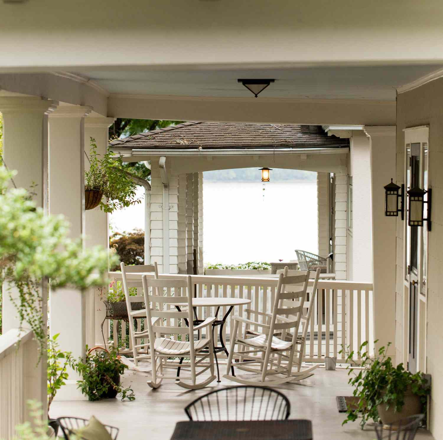 A deck outfitted with a table and several rocking chairs