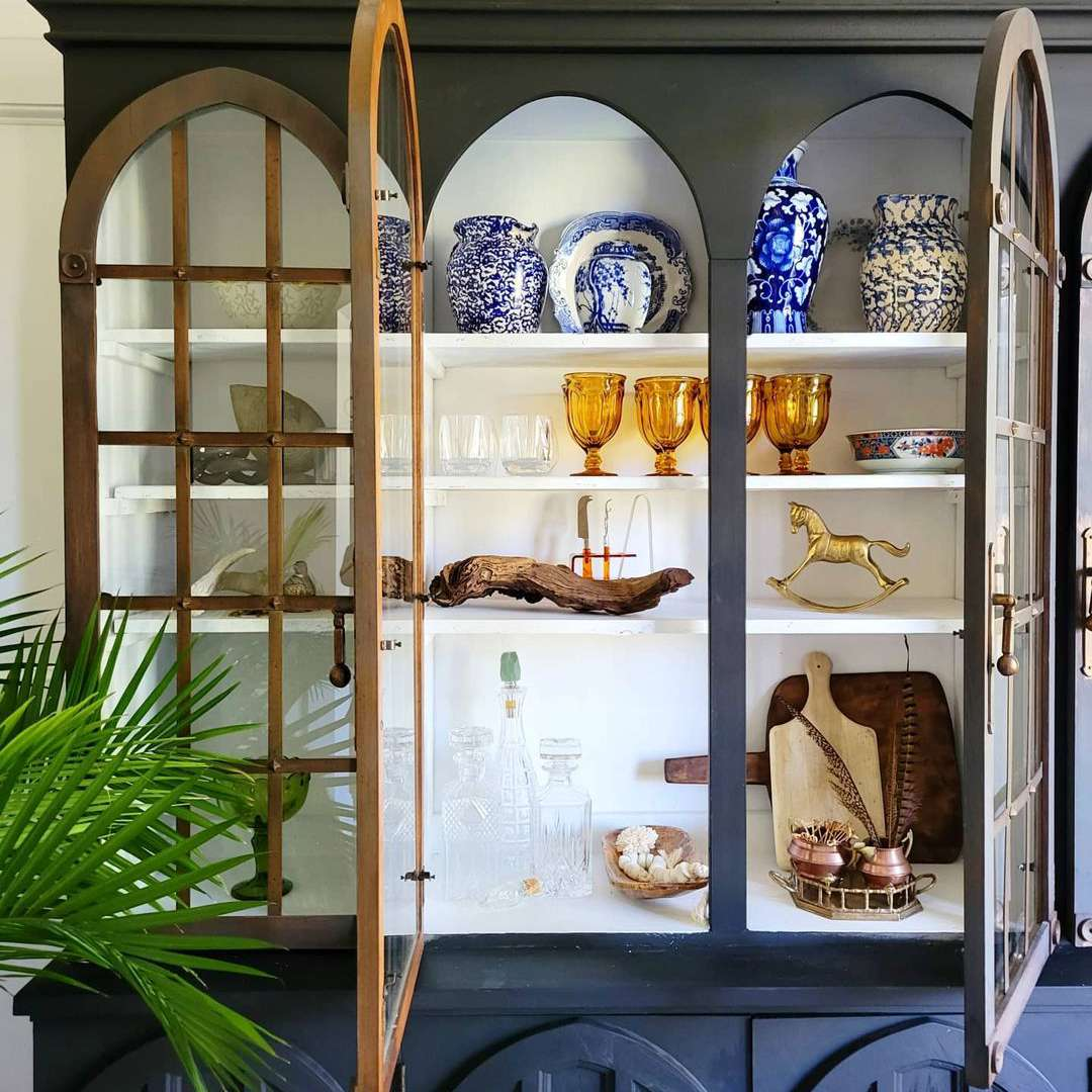 China cabinet filled with antique decor.