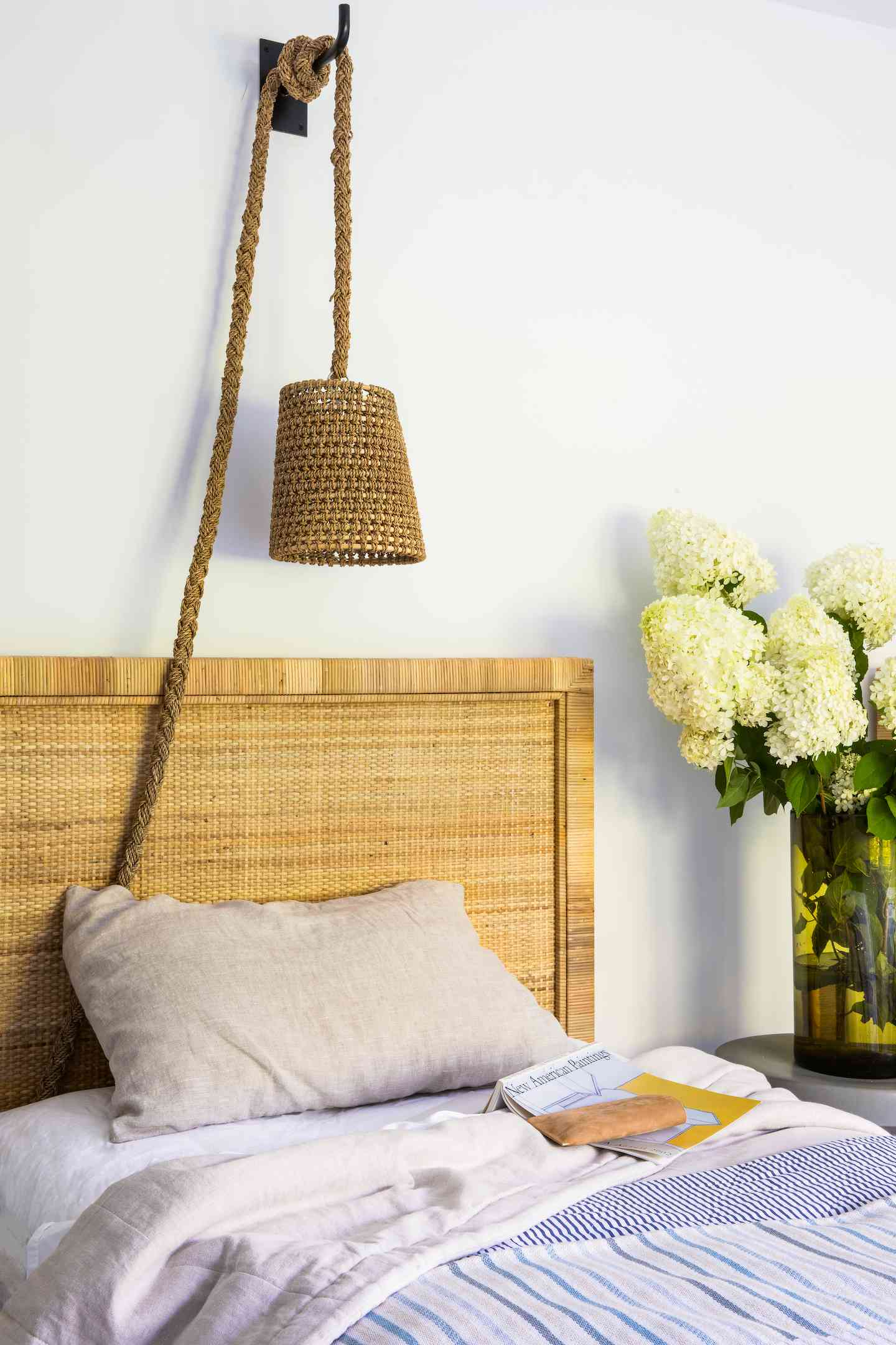 Bed with nautical rope lamp and side table with flowers.