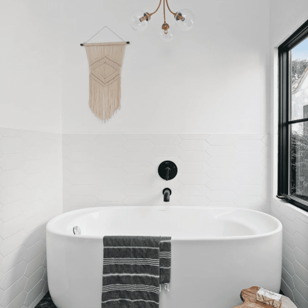 A bathroom with a white bathtub and charcoal tile-lined floors