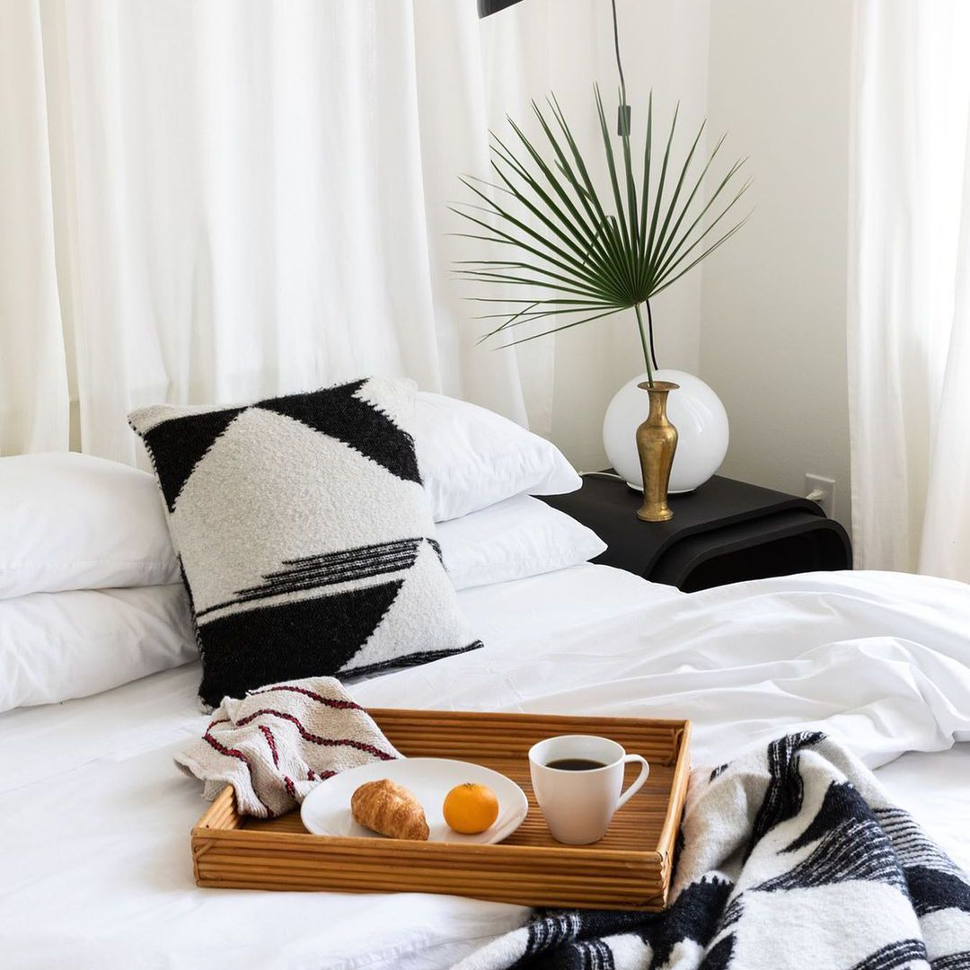 Cozy white bed with breakfast tray and palm frond.
