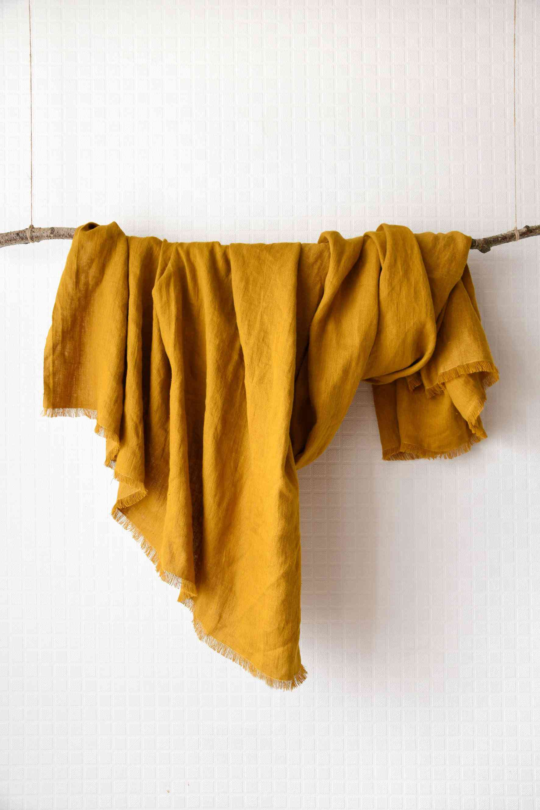 A mustard-colored linen throw draped over a branch.