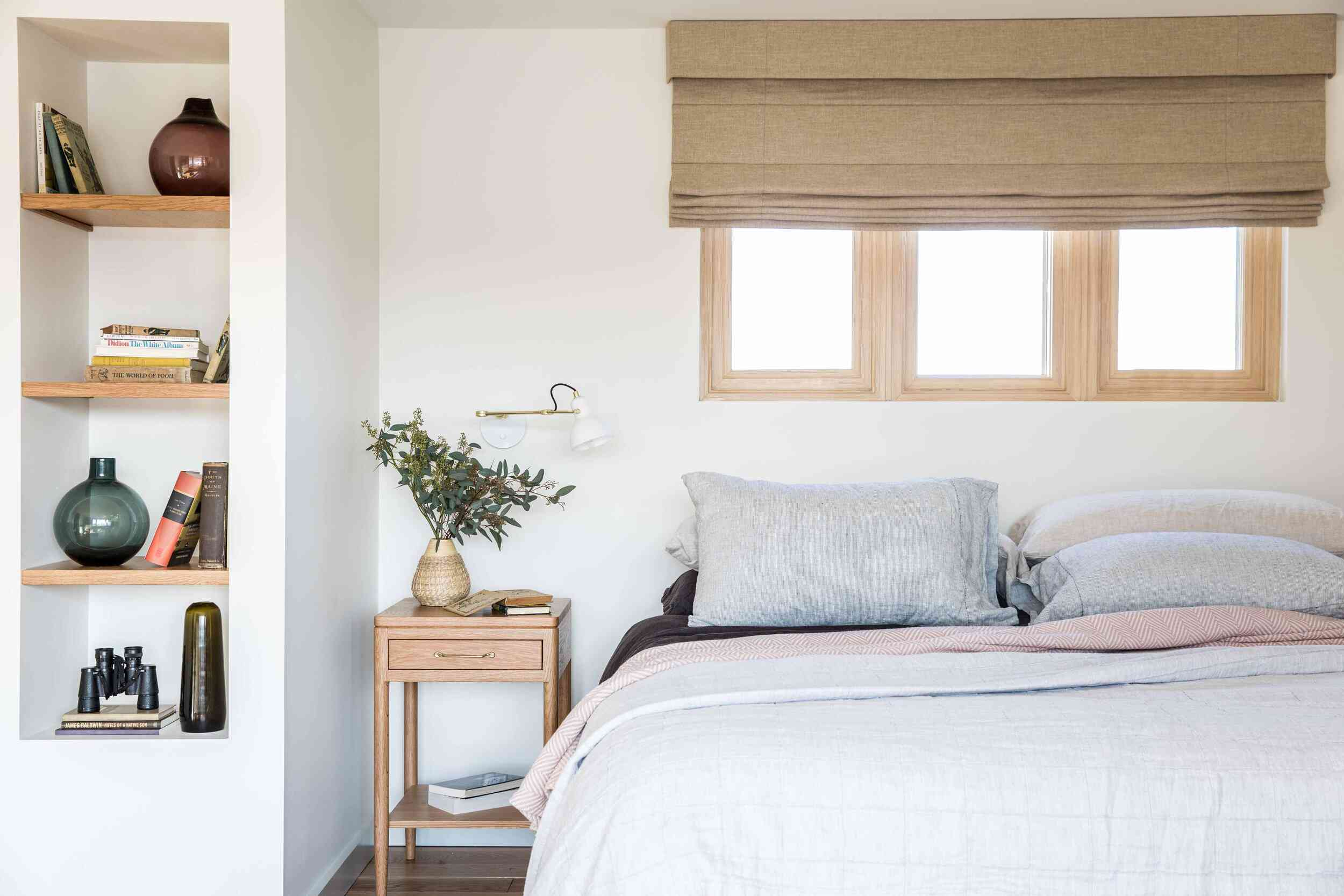 A bedroom with a small nightstand and several shelves that have been built-in to the wall