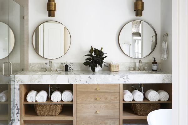 Marble bathroom vanity with light wooden drawers and double sinks.