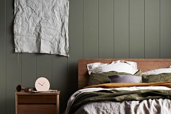 Moody green bedroom with midcentury furniture.