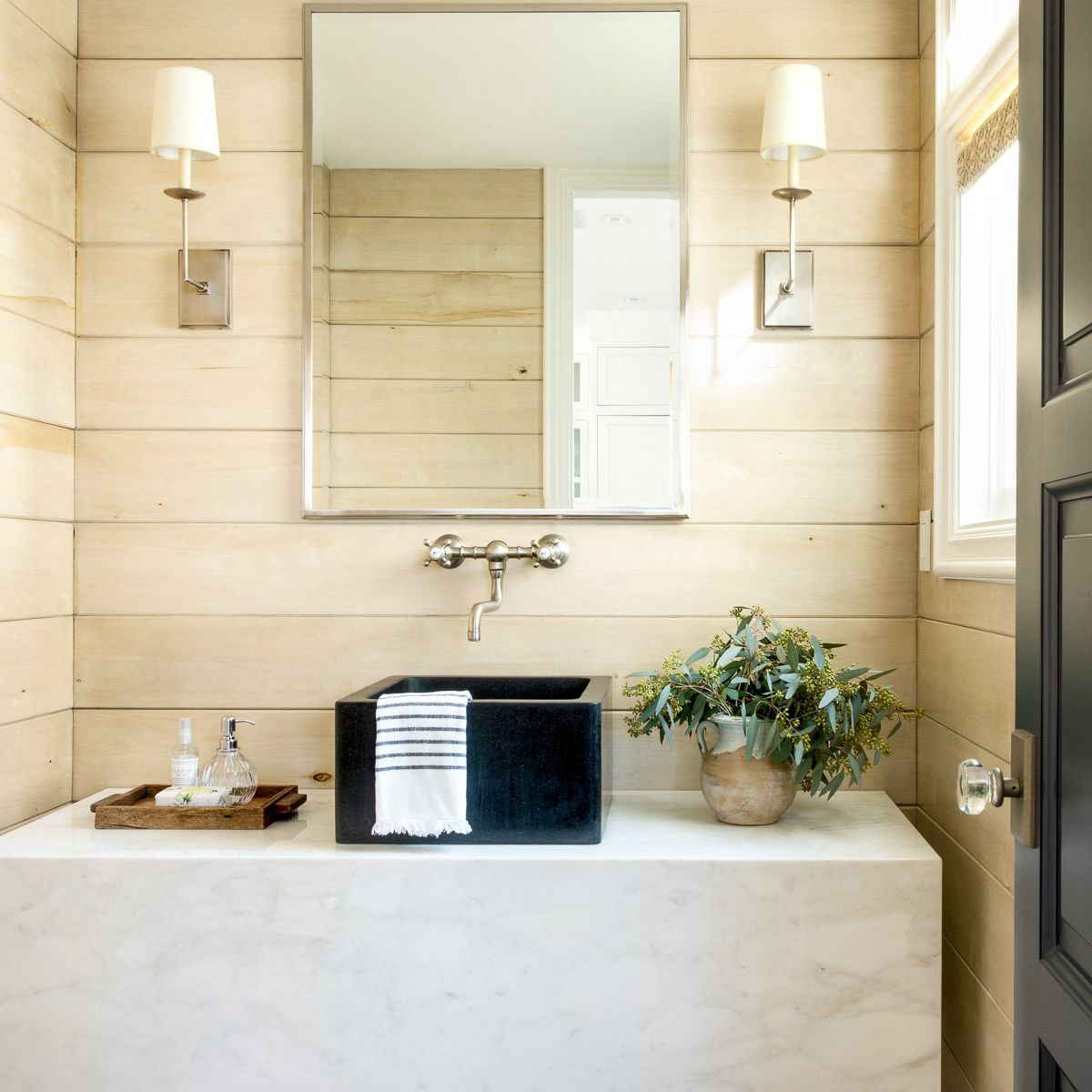 A bathroom with wood paneling lining the walls