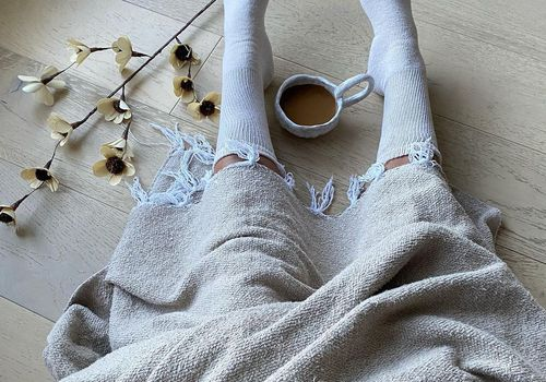 Cozy shot of woman with tea, blanket and plush socks.