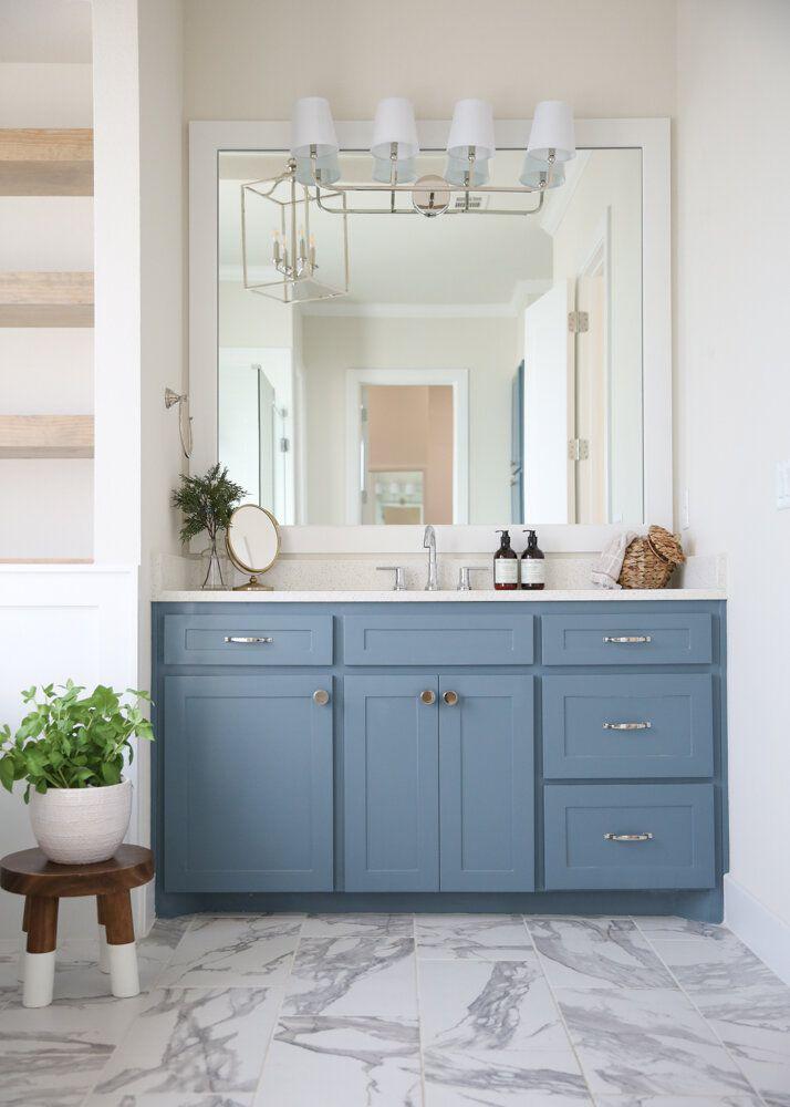 blue vanity in bathroom with large mirror