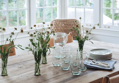 A wooden kitchen table topped with rustic vases of wildflowers