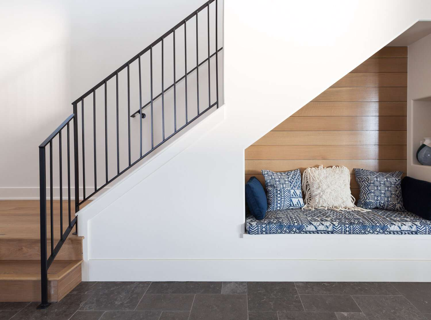 entryway that has sitting nook craved out in side of staircase