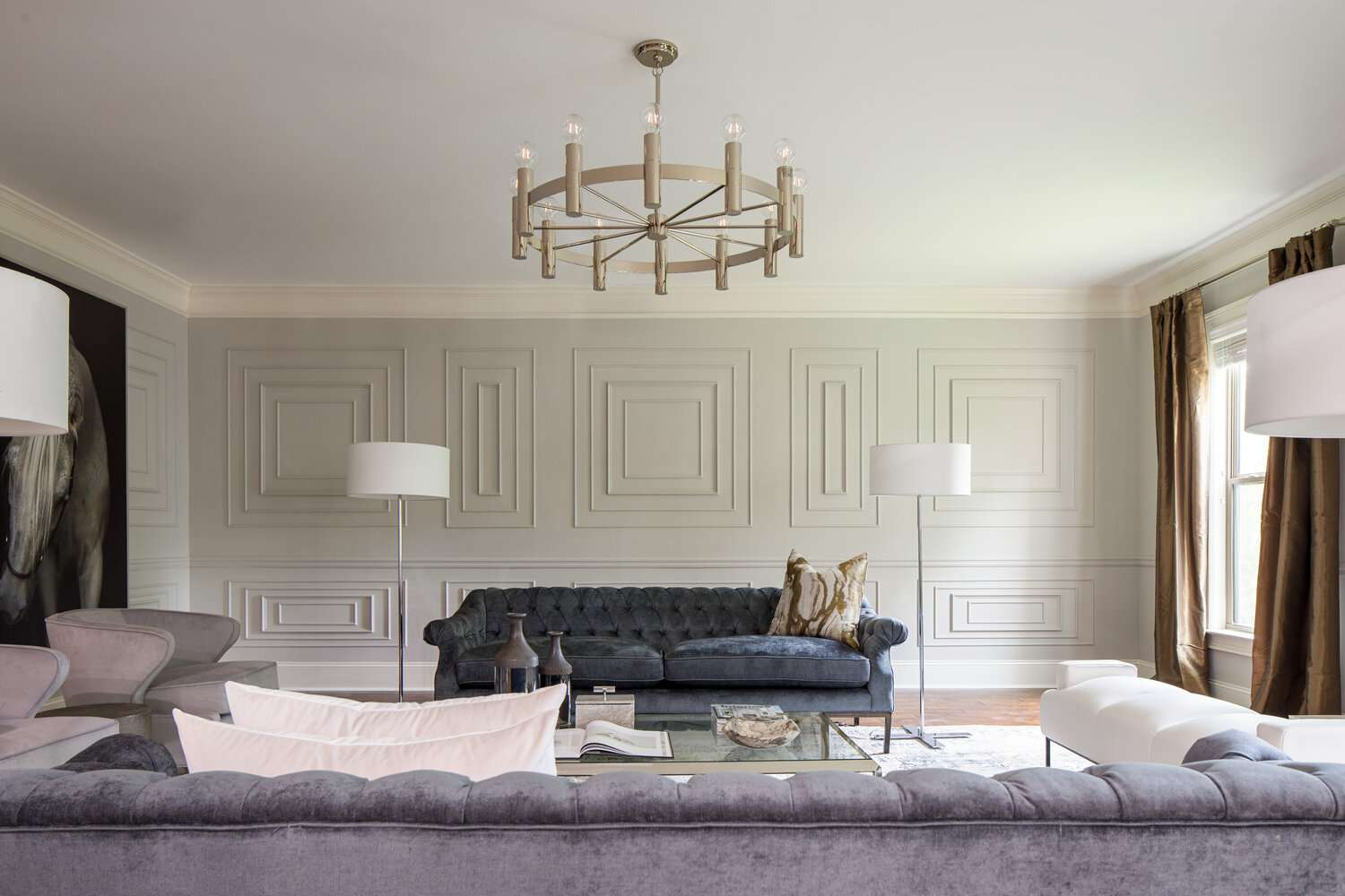 Chic, transitional living room with overhead lighting, natural light, and lamps