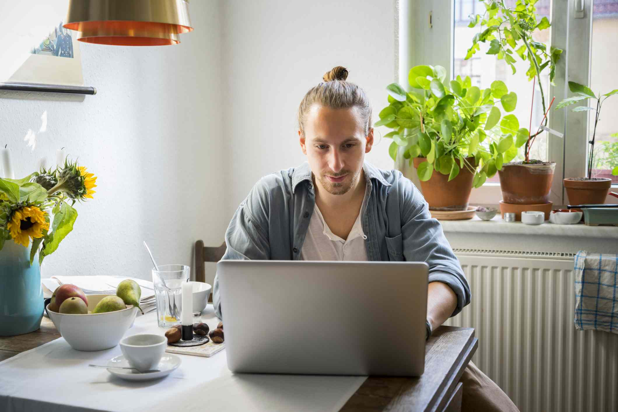 Young man uses laptop at dining table