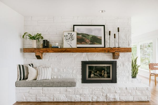 A white-painted stone fireplace topped by an extremely long wooden mantel