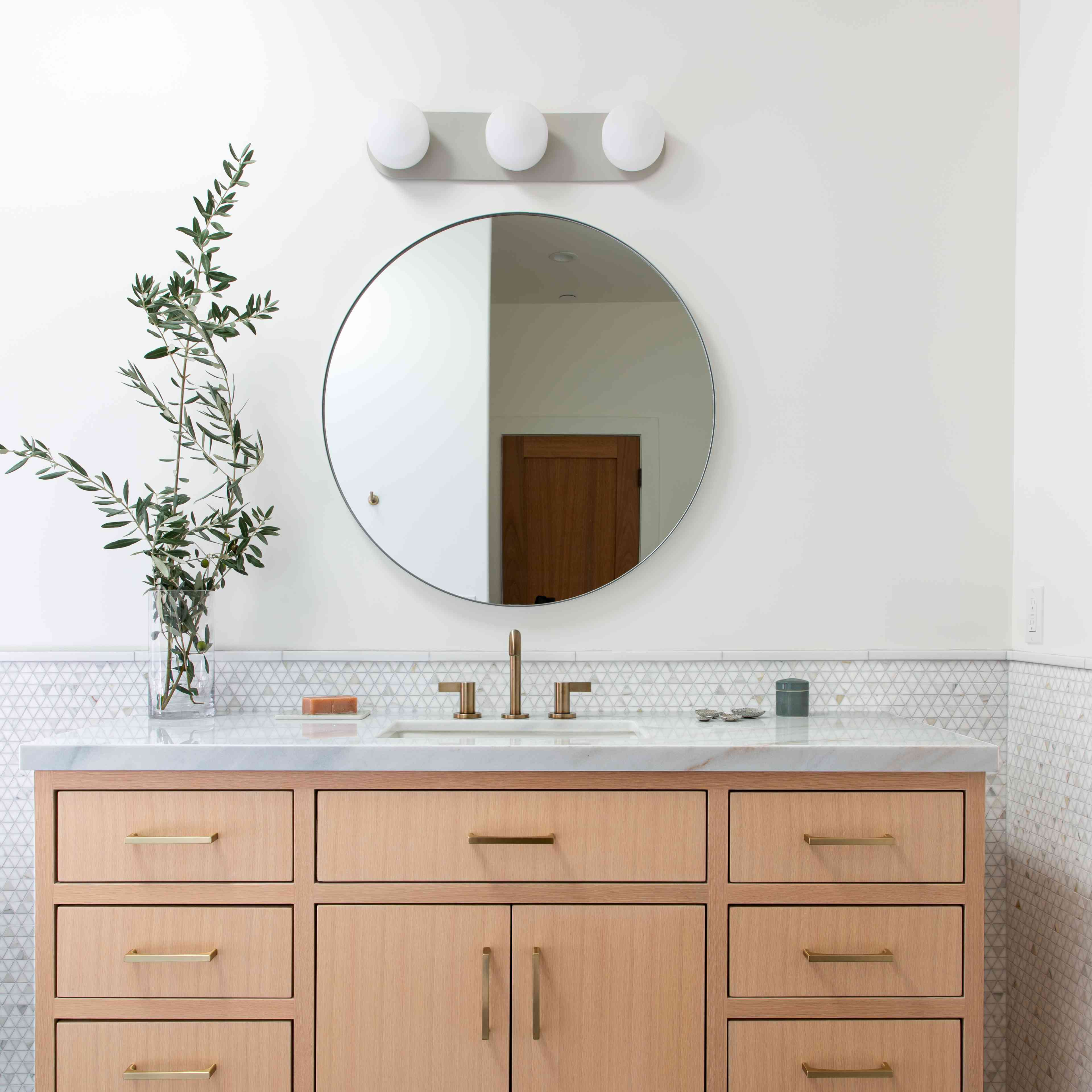 Neutral bathroom vanity with plant branches.