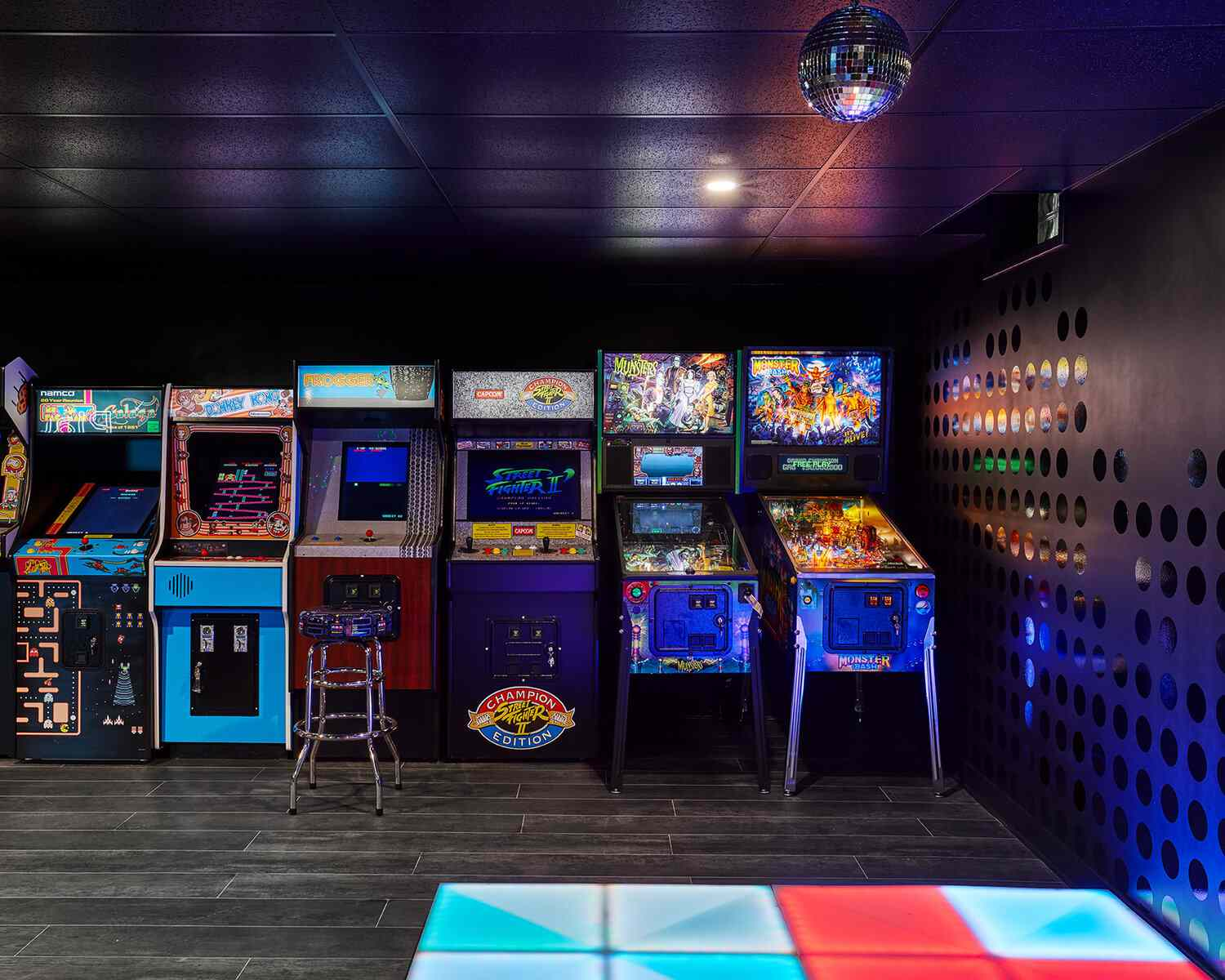 A basement filled with vibrant arcade games, which reflect off shiny accents on the wall and a disco ball on the ceiling