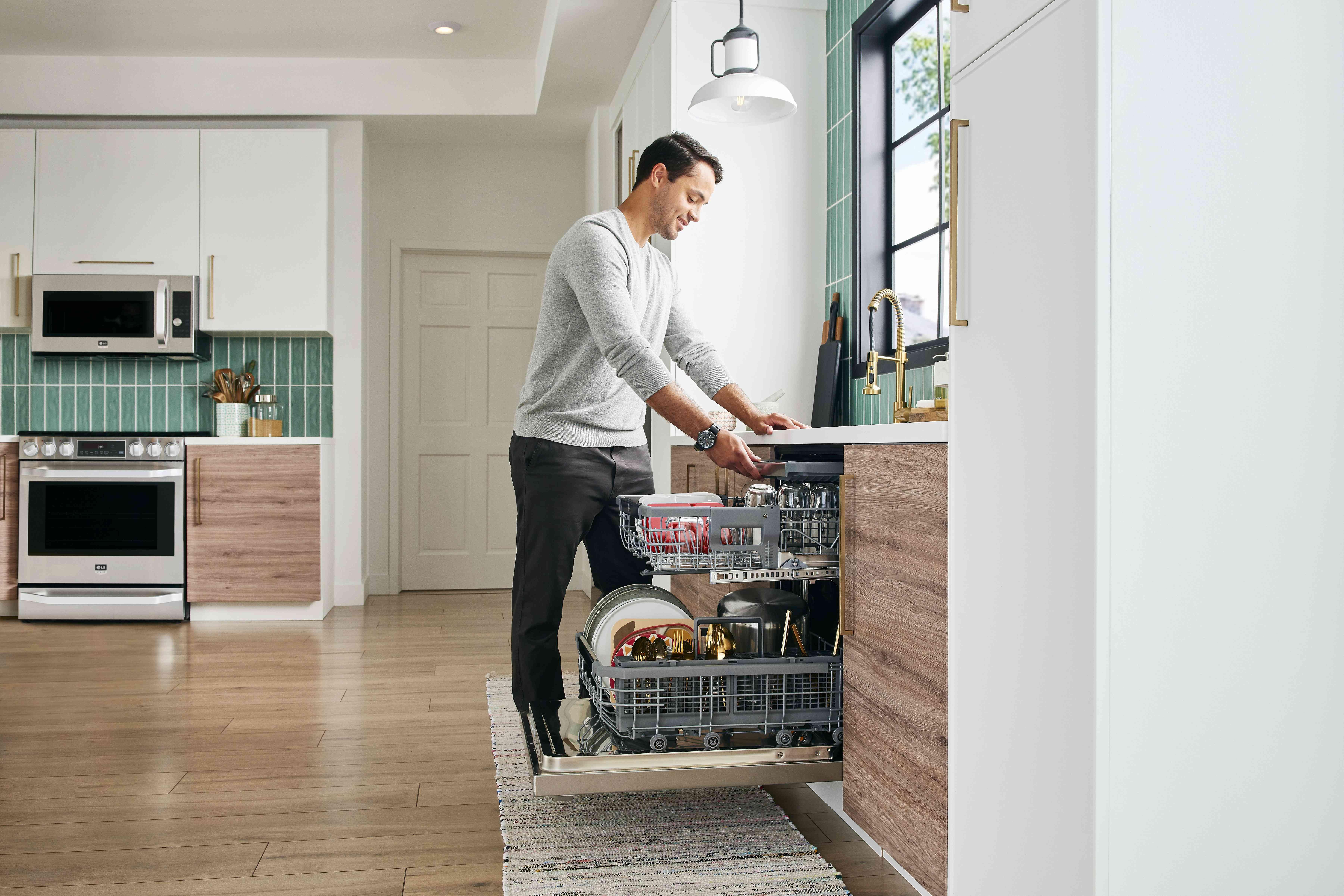Man loading LG Studio dishwasher
