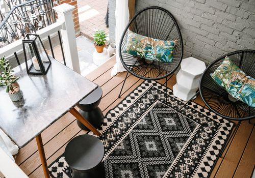 Overhead view of small outdoor space with black chairs.