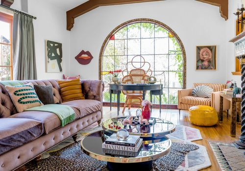 An interesting eclectic living area with a mix of furniture from different styles and eras.