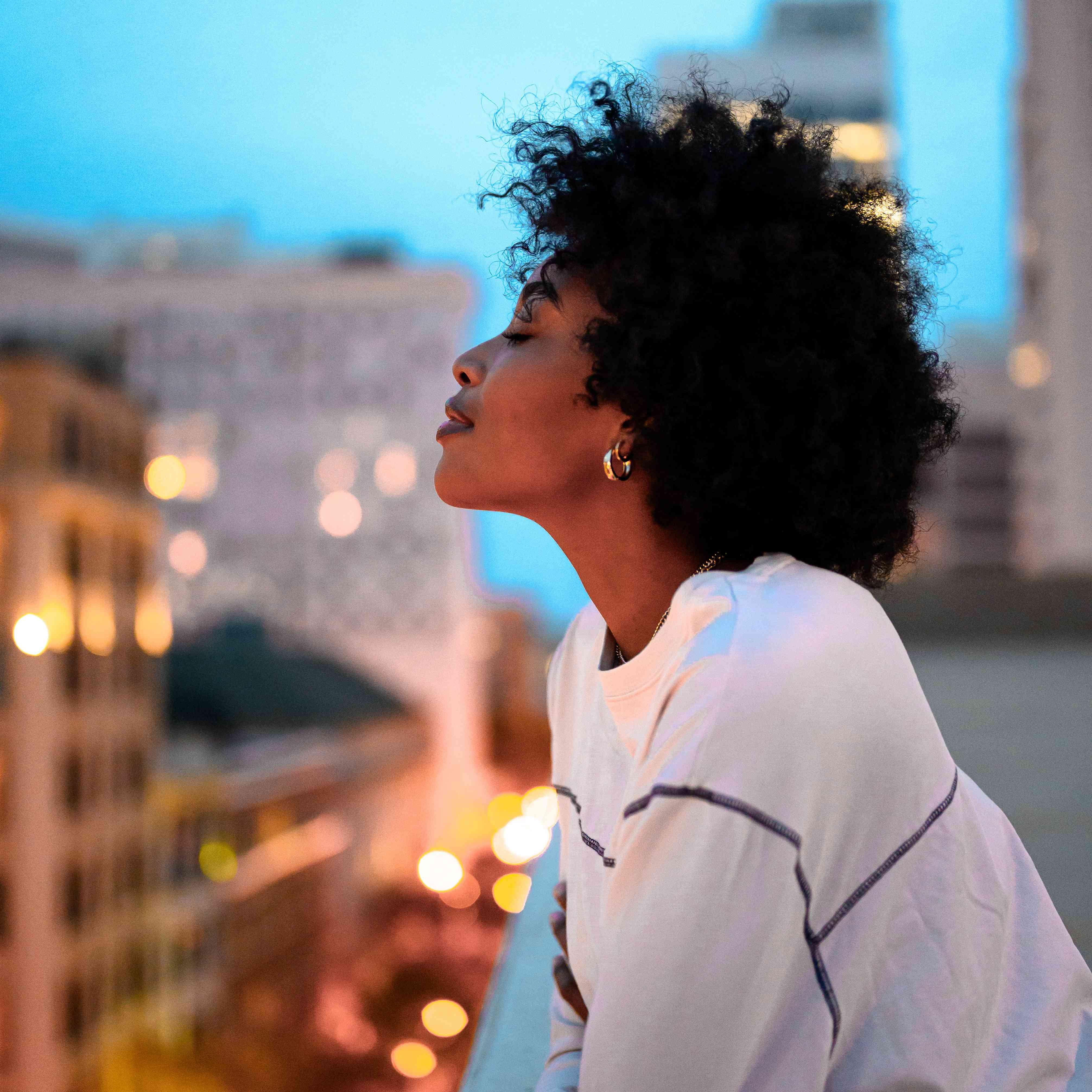 Mujer disfrutando de una brisa en un balcón
