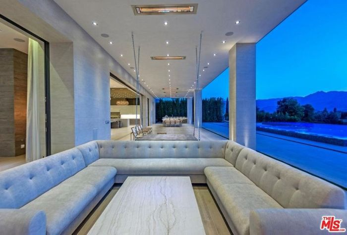A U-shaped wraparound sectional sofa just outside of a home with a roof overhead.