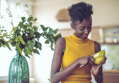 mujer pelando una fruta