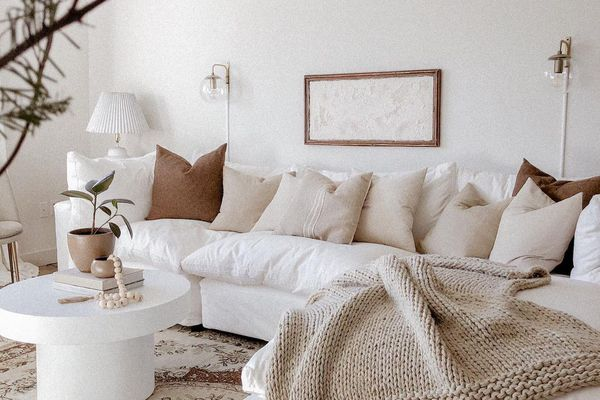 Neutral living room with large white sectional and brown pillows.